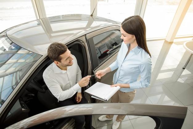 Młody człowiek w koncepcji jazdy próbnej wypożyczalni samochodów