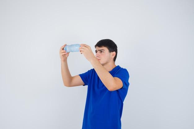 Młody człowiek w koszulce bada plastikową butelkę i patrząc uważnie, widok z przodu.