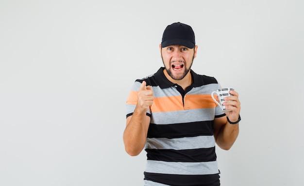 Młody człowiek w koszulce, czapce trzymającej kubek z napojem, ostrzegając palcem i patrząc zły, widok z przodu.