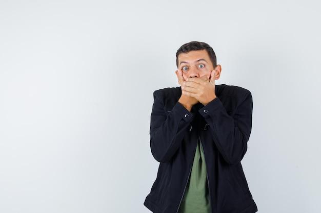 Młody człowiek w koszulce, kurtce, trzymając się za ręce na ustach i patrząc przestraszony, widok z przodu.