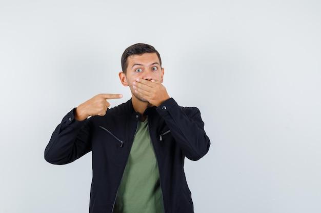 Młody człowiek w koszulce, kurtce, wskazując pod ręką na ustach i patrząc przestraszony, widok z przodu.