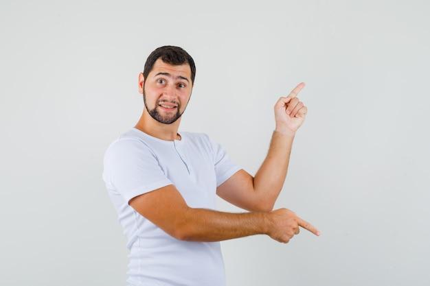Młody człowiek w koszulce, wskazując palcami w górę iw dół i patrząc skoncentrowany, widok z przodu.