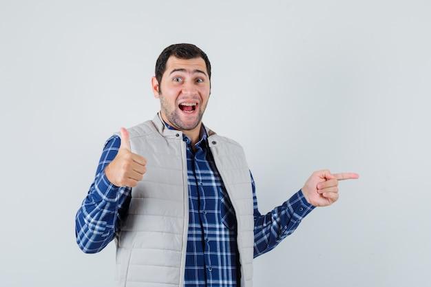 Młody człowiek w koszuli, bez rękawów, wskazując na bok, pokazując kciuk do góry i patrząc pozytywnie, widok z przodu.
