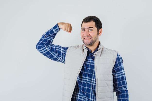 Młody człowiek w koszuli, bluzie bez rękawów, pokazując mięśnie ramion i patrząc pewnie, z przodu.