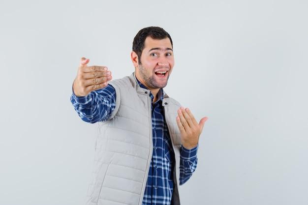 Młody człowiek w koszuli, bluzie bez rękawów, zaprasza kogoś blisko siebie i patrzy radośnie, widok z przodu.