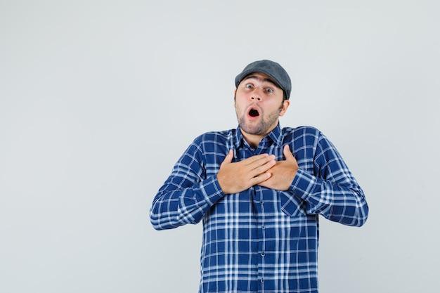 Młody człowiek w koszuli, czapce, trzymając się za ręce na klatce piersiowej i patrząc przestraszony, widok z przodu.