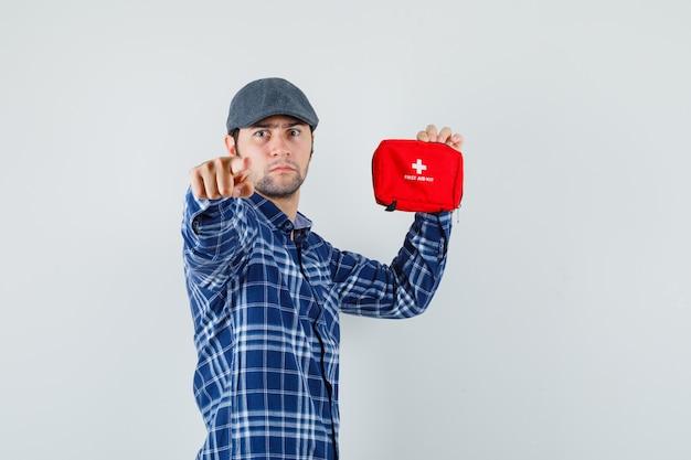 Młody człowiek w koszuli, czapka, wskazując na aparat, trzymając apteczkę i patrząc poważnie.