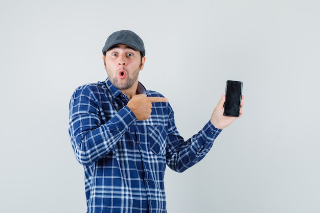 Młody człowiek w koszuli, czapka, wskazując na telefon komórkowy i patrząc zdziwiony, widok z przodu.