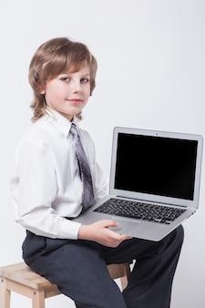 Młody człowiek w koszuli i krawata obsiadaniu z laptopem