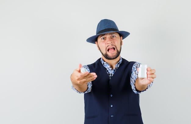 Młody człowiek w koszuli, kamizelce, kapeluszu, pokazuje otwartą butelkę pigułek i wygląda niespokojnie, widok z przodu.