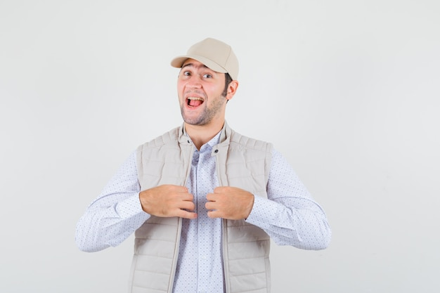 Młody człowiek w koszuli, kurtce bez rękawów, czapce trzymającej się za ręce na kołnierzu i wyglądający na zadowolonego, widok z przodu.