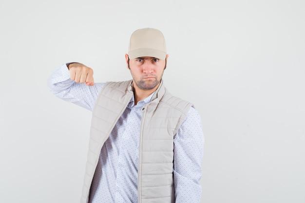Młody człowiek w koszuli, kurtce bez rękawów, czapce unoszącej pięść i agresywnie wyglądającej, widok z przodu.