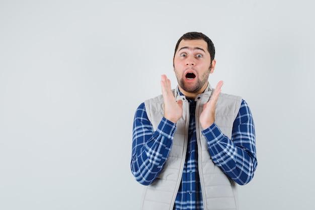 Młody człowiek w koszuli, kurtce bez rękawów, odwracając wzrok i patrząc przestraszony, widok z przodu. miejsce na tekst