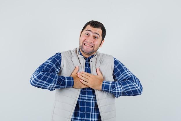 Młody człowiek w koszuli, kurtce bez rękawów, trzymając się za ręce na jego klatce piersiowej i patrząc podekscytowany, widok z przodu.