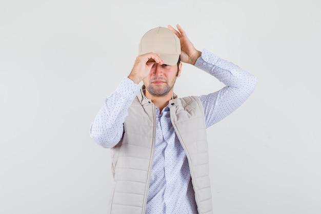 Młody człowiek w koszuli, kurtce bez rękawów w czapce i wyglądający pewnie, widok z przodu.