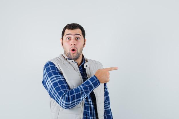 Młody człowiek w koszuli, kurtce bez rękawów, wskazując na bok i patrząc przerażony, widok z przodu.