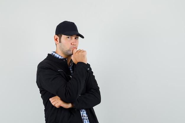 Młody człowiek w koszuli, kurtce, czapce stojącej w myśleniu poza i patrząc poważnie