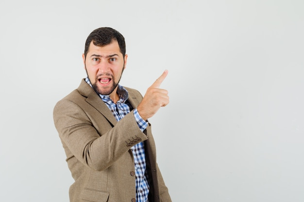 Młody człowiek w koszuli, kurtce ostrzegawczej z palcem i patrząc nerwowo, widok z przodu.