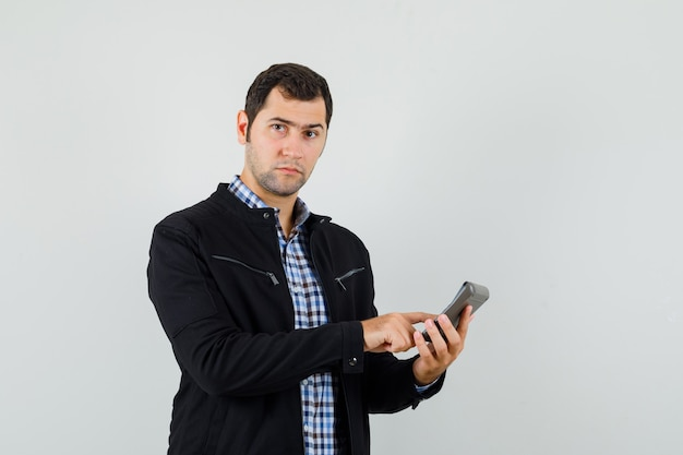 Młody człowiek w koszuli, kurtce, wykonując obliczenia na kalkulatorze i wyglądający rozsądnie