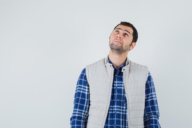 Młody człowiek w koszuli, kurtka bez rękawów, patrząc w górę, widok z przodu. miejsce na tekst