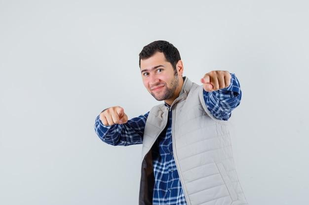 Młody człowiek w koszuli, kurtka bez rękawów, wskazując do przodu i patrząc radośnie, widok z przodu.