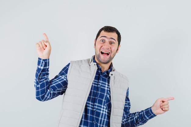 Młody człowiek w koszuli, kurtka bez rękawów, wskazując na różne strony i patrząc radośnie, widok z przodu.