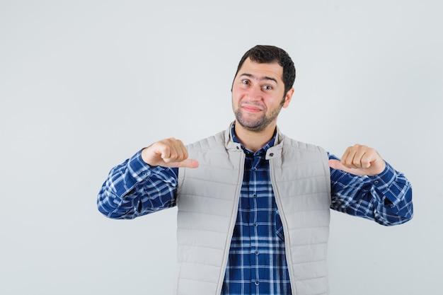 Młody człowiek w koszuli, kurtka bez rękawów, wskazując na siebie i patrząc pewnie, widok z przodu.