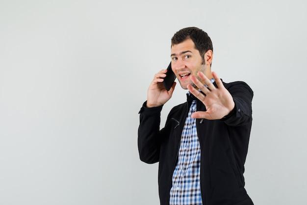 Młody człowiek w koszuli, marynarce rozmawia przez telefon komórkowy, robi gest oczekiwania i wygląda pozytywnie