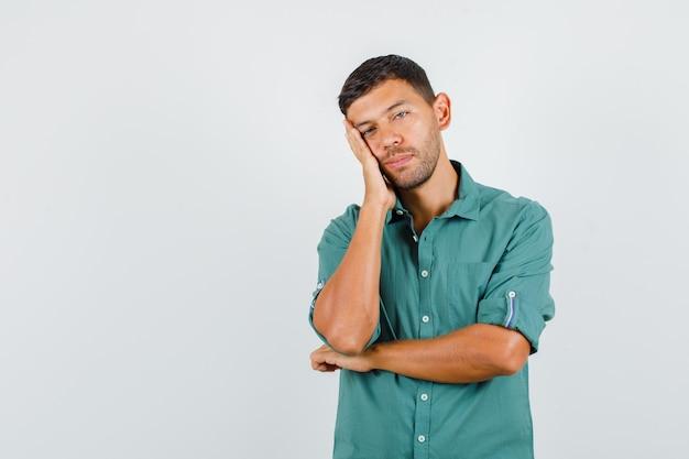 Młody człowiek w koszuli, opierając policzek na uniesionej dłoni i wyglądający na zmęczonego