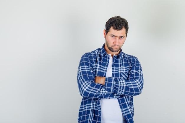 Młody człowiek w koszuli stojący ze skrzyżowanymi rękami i wyglądający ponuro