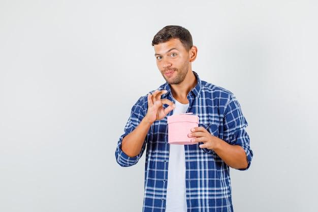 Młody człowiek w koszuli, trzymając pudełko z ok znak i patrząc wesoło, widok z przodu.