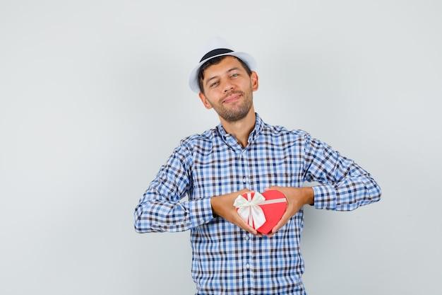 Młody człowiek w kraciastej koszuli, kapeluszu pokazującym pudełko i wyglądający wesoło
