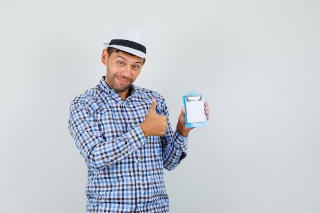 Młody człowiek w kraciastej koszuli, kapeluszu, trzymając mini schowek
