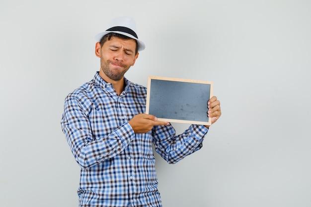 Młody człowiek w kraciastej koszuli, kapeluszu, trzymając pustą ramkę z zamkniętymi oczami