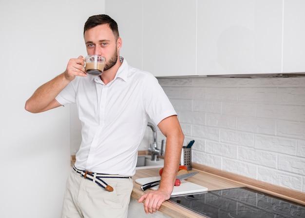 Młody człowiek w kuchni cieszy się kawę