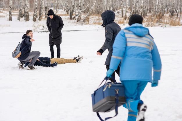 Młody człowiek w kucki nad chorym leżącym w śniegu z prośbą o pomoc, patrząc na ratowników medycznych na zewnątrz w zimie