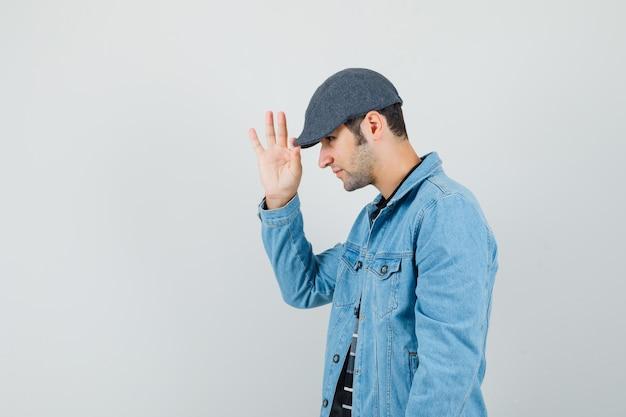 Młody człowiek w kurtce, koszulce dotykając czapki i wyglądający na spokojnego. miejsce na tekst