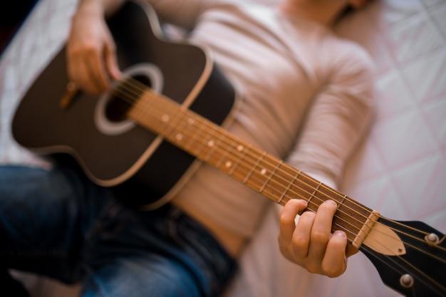 Młody człowiek w lekkiej bluzie i dżinsach gra rano na łóżku na gitarze akustycznej