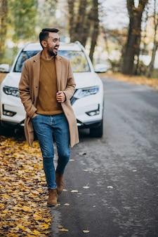 Młody człowiek w lesie na sobie płaszcz przez samochód