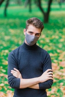 Młody człowiek w masce grypy w jesiennym parku