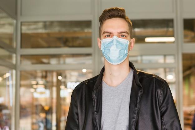 Młody człowiek w masce medycznej. kwarantanna bezpieczeństwa. mężczyzna w sklepie