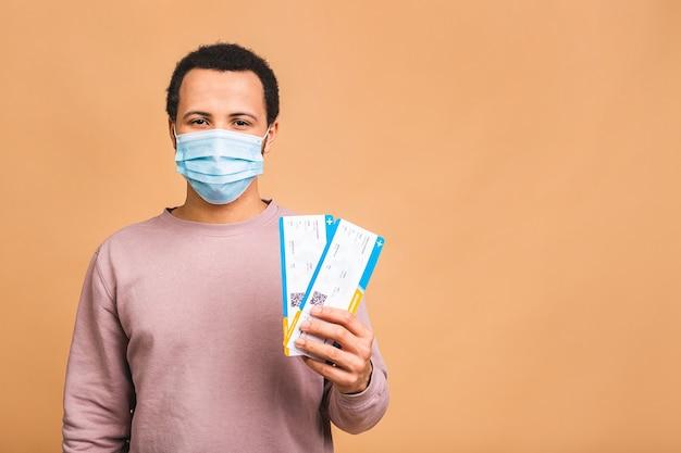 Młody człowiek w masce ochronnej holding pokładowe bilety na białym tle nad beżowym