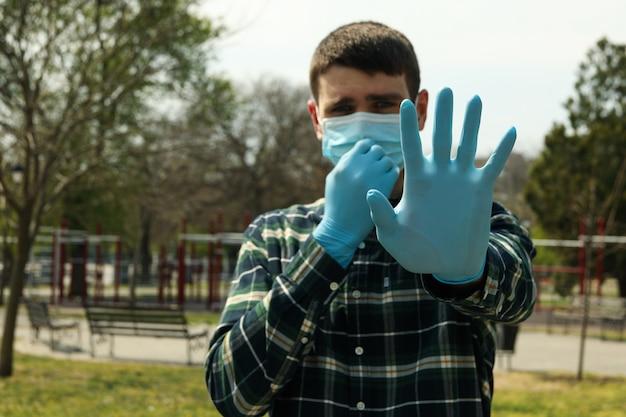 Młody człowiek w masce ochronnej i rękawiczkach w parku