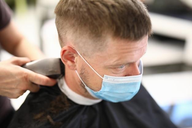 Młody człowiek w masce ochronnej na twarzy sprawia, że fryzura w salonie piękności portret