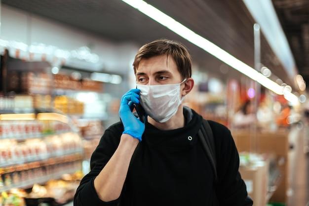 Młody człowiek w masce ochronnej rozmawia na swoim smartfonie