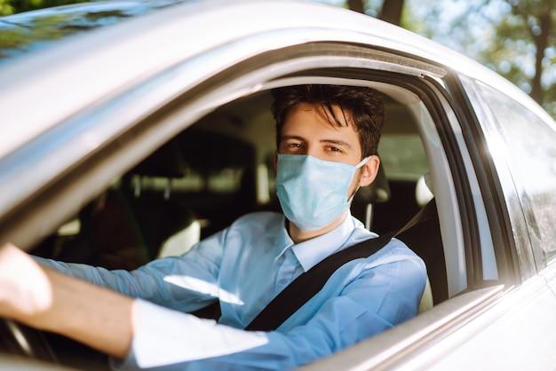 Młody człowiek w masce ochronnej siedzi w samochodzie