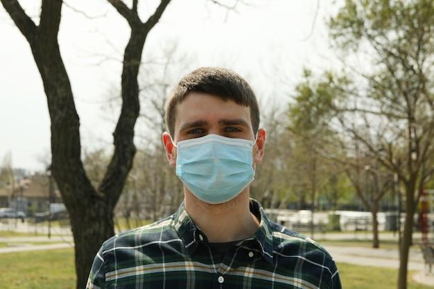 Młody człowiek w masce ochronnej w parku