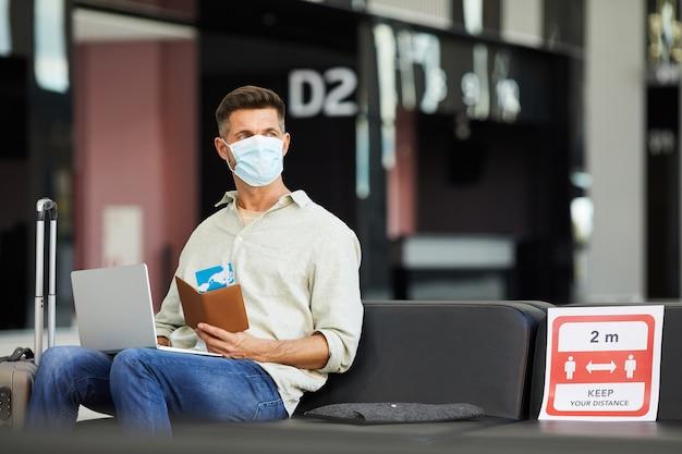 Młody człowiek w masce ochronnej z bagażem i biletami siedzi na lotnisku podczas pandemii