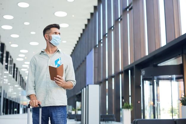 Młody człowiek w masce ochronnej z bagażem i biletami stojąc na lotnisku