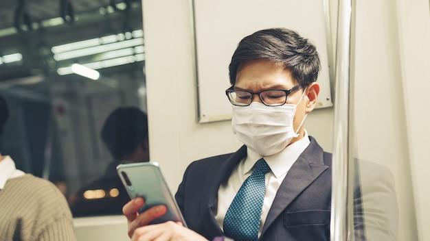 Młody człowiek w masce podróżuje zatłoczonym pociągiem metra